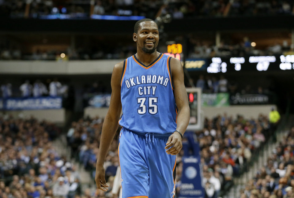 Photo - Oklahoma City Thunder's Kevin Durant (35) smiles as he walks back to the bench after sinking a basket against the Dallas Mavericks in the second half of an NBA basketball game, Friday, Jan. 22, 2016, in Dallas. Durant scored 24 points in the former Texas star's first game in Dallas in almost two years, and the Thunder extended their winning streak to a season-best seven games by holding on for a 109-106 victory over the Mavericks on Friday night. (AP Photo/Tony Gutierrez)