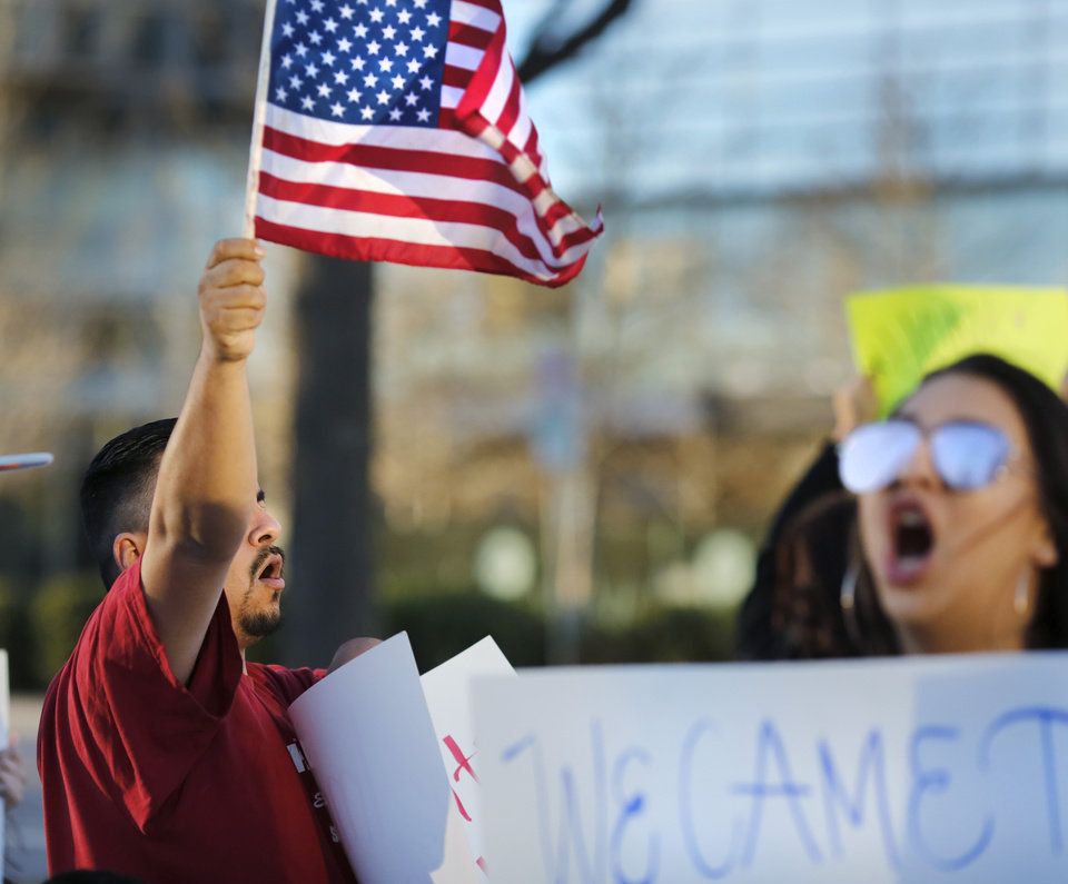 Photo - More than two dozen protestors waved American flags, held signs and chanted pro-immigration slogans late Thursday afternoon, Feb. 16, 2017,  in downtown Oklahoma City. The local protest, at the southwest corner of Sheridan Avenue and Ron Norick, was part of a national event staged to point out the impact on the national economy that immigrants bring. Photo by Jim Beckel, The Oklahoman