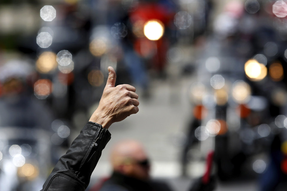 Photo -  One of the early riders to arrive at the Memorial gives a thumbs up to fellow bikers as they turn onto N Harvey Avenue from NW 5 Street as part of the 10th annual Ride to Remember. [Photo by Jim Beckel, The Oklahoman]