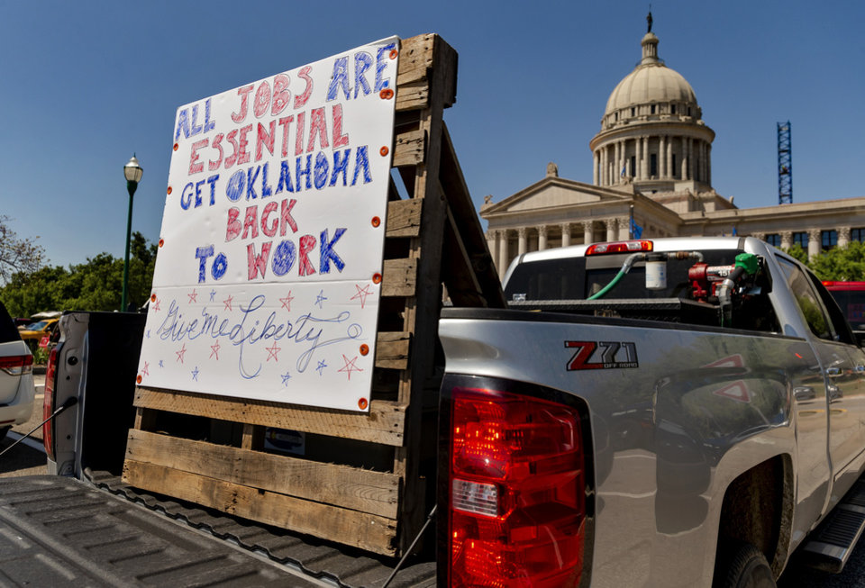 Photo -  A protester displays a sign in the back of a pickup during a rally Wednesday at the Capitol. [Chris Landsberger/The Oklahoman]