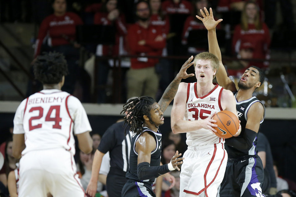 Photo - Oklahoma's Brady Manek (35) tries to pass the ball as Kansas State's Cartier Diarra (2), left, and Antonio Gordon (11) defend during an NCAA college basketball game between the University of Oklahoma Sooners (OU) and the Kansas State Wildcats at Lloyd Noble Center in Norman, Okla., Saturday, Jan. 4, 2020. [Bryan Terry/The Oklahoman]