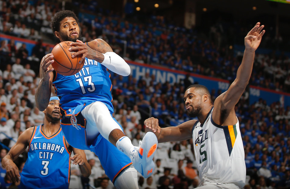 Photo -  Oklahoma City's Paul George grabs a rebound beside Utah's Derrick Favors during Game 5 of the first-round NBA Playoffs at Chesapeake Energy Arena on April 25. [Photo by Bryan Terry, The Oklahoman Archives]