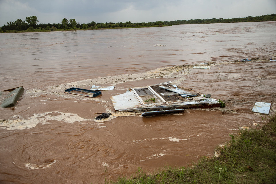 Photo - Debris is washed down the river from an abandoned home after it was washed away by the flood waters rushing down the river in the Twin Lakes community near Cimarron City, Okla. on Wednesday, May 22, 2019.  [Chris Landsberger/The Oklahoman]