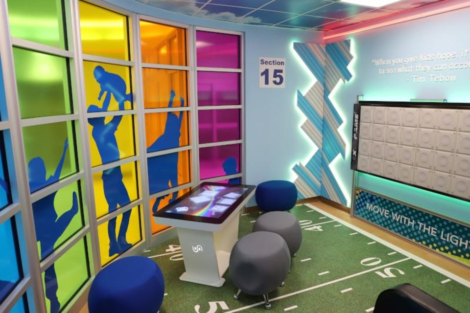 Photo - Timmy's Playroom includes a football field floor and custom-built lockers for seating. [PHOTO PROVIDED]