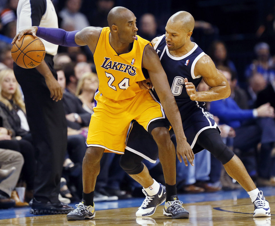 Photo - LA's Kobe Bryant (24) keeps the ball away from Oklahoma City's Derek Fisher (6) during an NBA basketball game between the Los Angeles Lakers and the Oklahoma City Thunder at Chesapeake Energy Arena in Oklahoma City, Friday, Dec. 13, 2013. Photo by Nate Billings, The Oklahoman