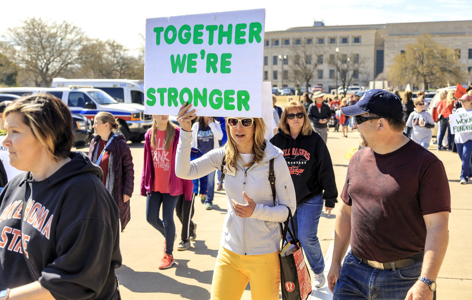 Photo - Edmond Memorial teacher Christine Custred, center, marches around the Capitol with fellow teachersduring the ninth day of a walkout by Oklahoma teachers at the state Capitol in Oklahoma City, Okla. on Tuesday, April 10, 2018.   Photo by Chris Landsberger, The Oklahoman