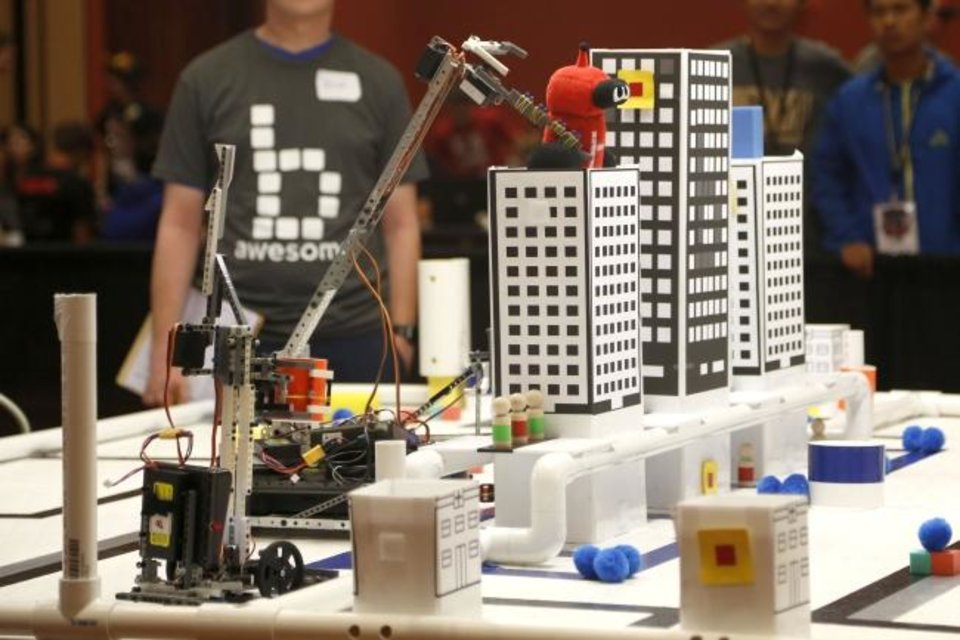 Photo -  A robot in the Botball seeding on Monday lifts a toy from the top of the track at the Global Conference on Educational Robotics in Norman. [PAXSON HAWS/THE OKLAHOMAN]