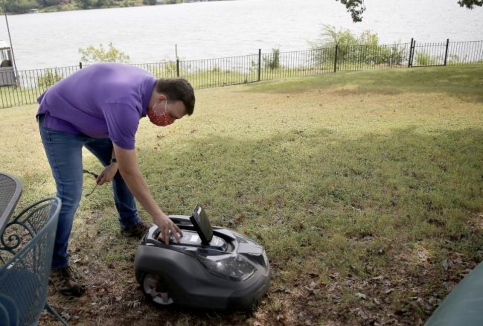 Photo -  Connor Pearson with MowBot of Central Oklahoma sets up a robotic mower Tuesday in Arcadia. [SARAH PHIPPS/THE OKLAHOMAN]