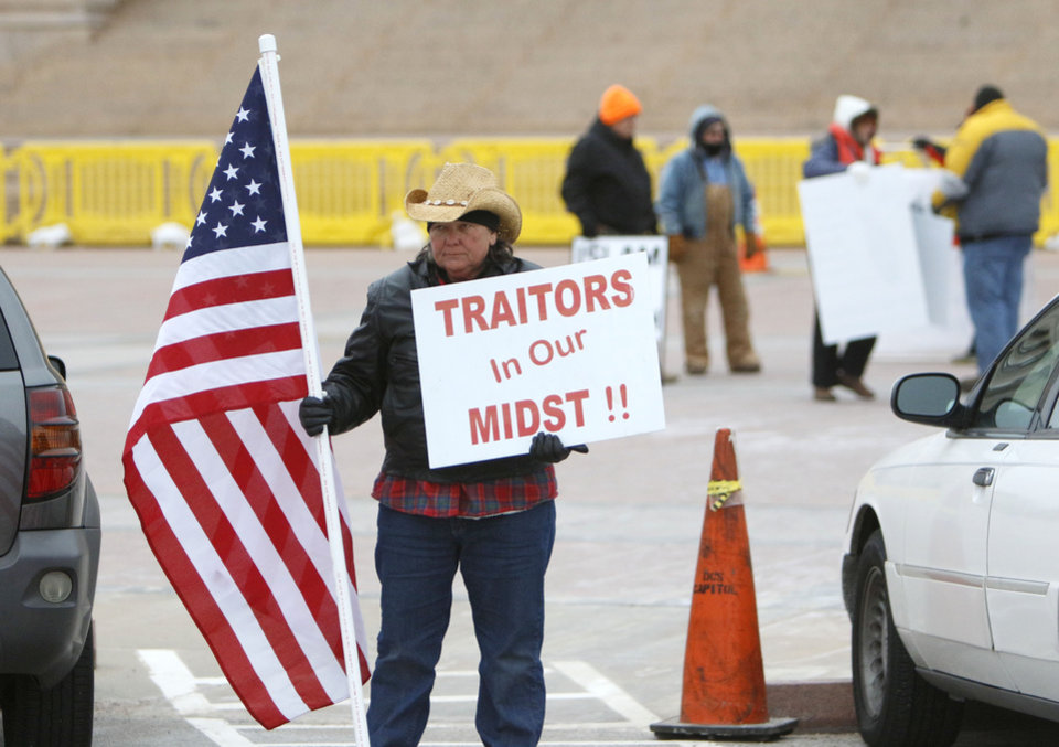 Photo - Liz Cockrell holds a sign and flag in protest as CAIR and local Muslims gather at the State Capitol in Oklahoma City, OK, for Oklahoma Muslim Day, Friday, February 27, 2015,  Photo by Paul Hellstern, The Oklahoman