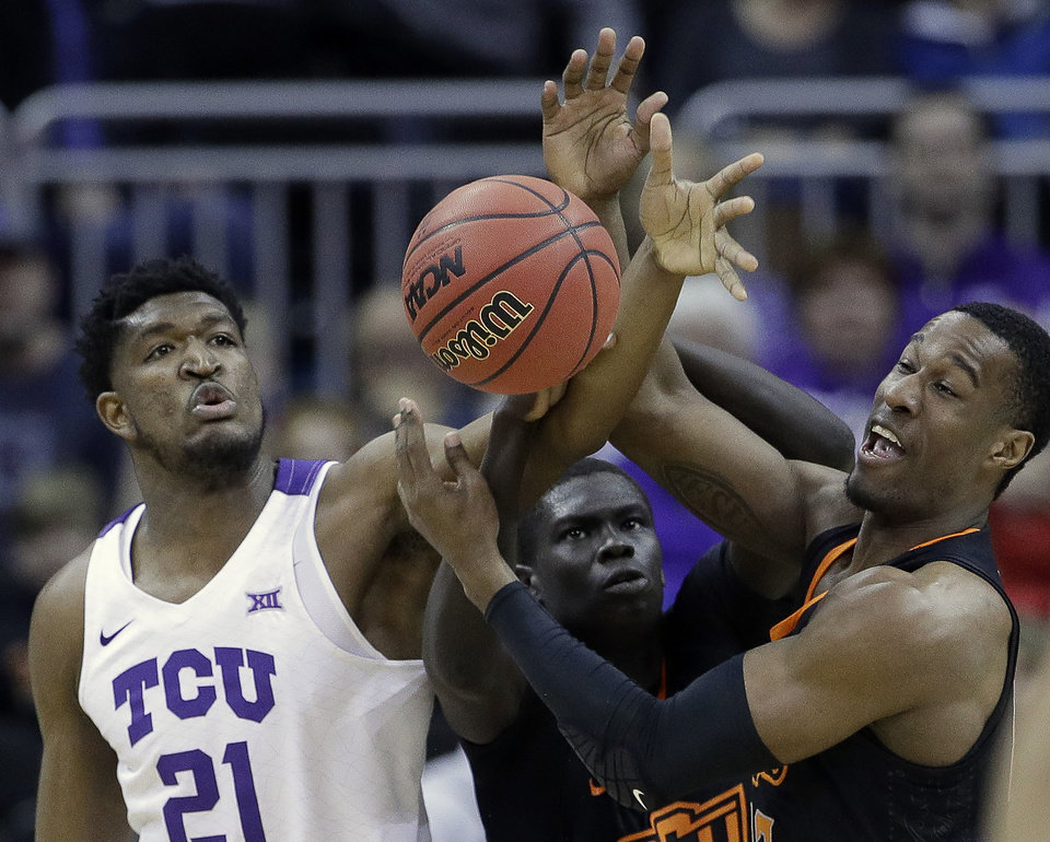 Photo - TCU's Kevin Samuel (21) competes for a rebound against Oklahoma State's Cameron McGriff, right, and Yor Anei during the first half of an NCAA college basketball game in the Big 12 men's tournament Wednesday, March 13, 2019, in Kansas City, Mo. (AP Photo/Charlie Riedel)