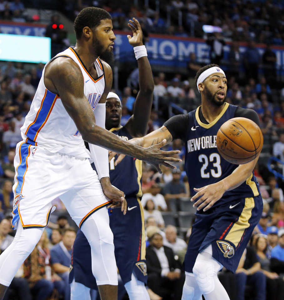 Photo - Oklahoma City's Paul George (13) passes away from New Orleans' Anthony Davis (23) and Jrue Holiday (11) in the second quarter during a preseason NBA basketball game between the Oklahoma City Thunder and the New Orleans Pelicans at Chesapeake Energy Arena in Oklahoma City, Friday, Oct. 6, 2017. Photo by Nate Billings, The Oklahoman