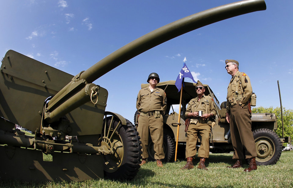 Photo - A group of docents at the 45th Infantry Division Museum dressed in authentic World war II uniforms lean against a 1942 Jeep manufactured by Ford Motor Co. In foreground is a 1941 37mm anti-tank gun that was fired to begin the day's activities during the Memorial Day observance in Oklahoma City, Monday,  May 31, 2010. Photo by Jim Beckel, The Oklahoman