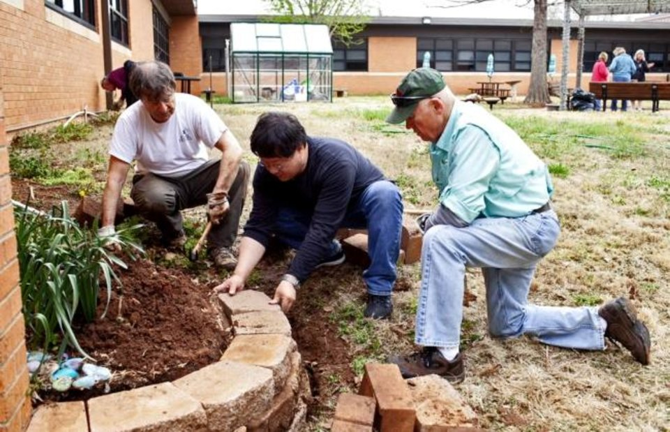 Photo -  From left, Tom Langdon, John Yim and Sid Brown work with landscape bricking to improve the look of Central Middle School's courtyard. [PHOTO PROVIDED]