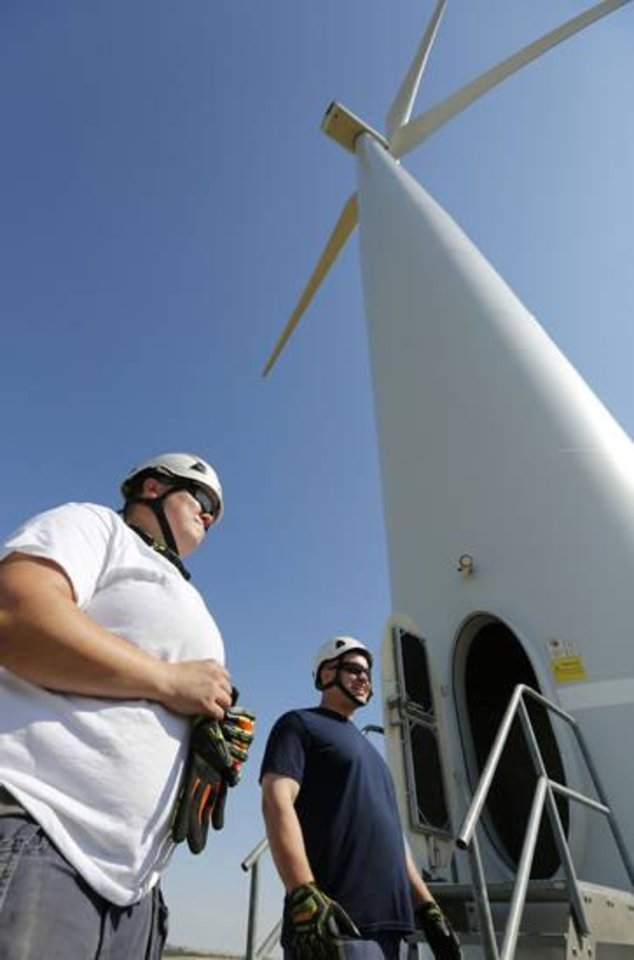 Photo -  NextEra Energy Resources technicians Crys Matthews and Matthew Linthicum prepare to scale a 280 ft. wind turbine in Minco. [Photo by Paul Hellstern, The Oklahoman]