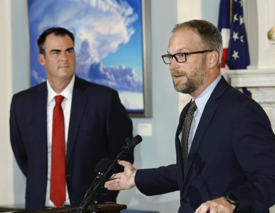 Photo -  Justin Brown answers reporters' questions after being in introduced by Gov. Kevin Stitt, left, during a press conference at the state Capitol Tuesday morning, June 4, 2019. The governor said Brown has been selected to run the Oklahoma Department of Human Services and replaces current DHS director Ed Lake.  Brown is the CEO of a company that has multiple assisted living facilities in Oklahoma and neighboring states.   [Jim Beckel/The Oklahoman]