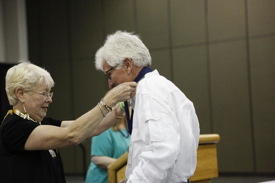 Photo - Daniel Worcester receives first place for the diversified arts category from Teri Stanek, past president of the Red Earth board, during the 2019 Red Earth Festival at the Cox Convention Center in Oklahoma City, Oklahoma Friday, June 7, 2019. [Paxson Haws/The Oklahoman]