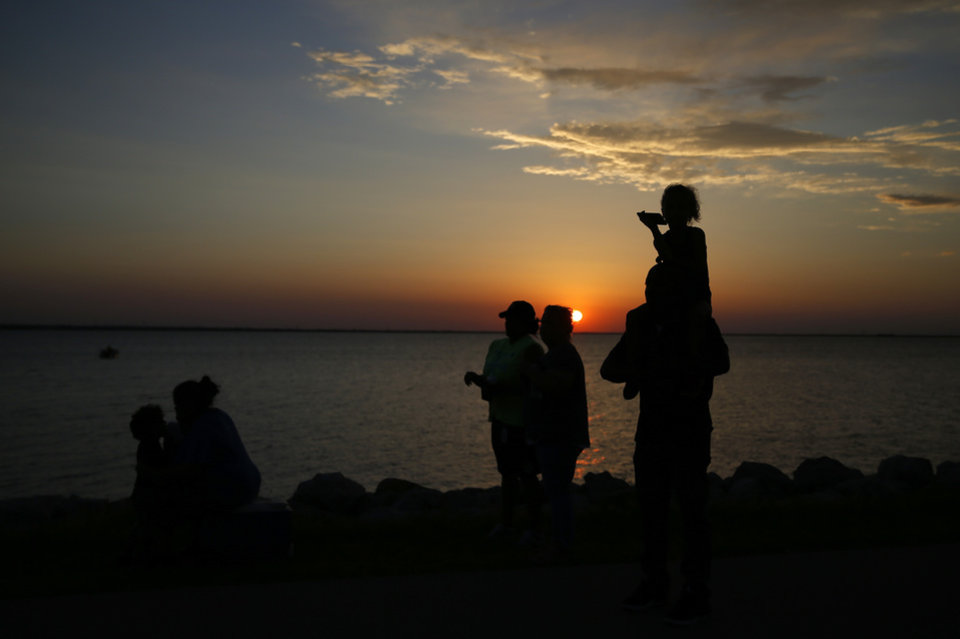Photo - People wait to be allowed to return to their cars as the sun sets following a shooting on the east side of Lake Hefner in Oklahoma City, Thursday, May 24, 2018. Photo by Sarah Phipps, The Oklahoman