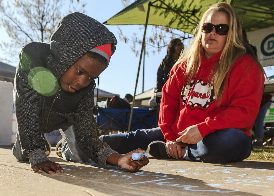 Photo - Teacher Jennifer Shaw does some sidewalk math with kindergartner Titus Shaw during the ninth day of a walkout by Oklahoma teachers at the state Capitol in Oklahoma City, Okla. on Tuesday, April 10, 2018.   Photo by Chris Landsberger, The Oklahoman