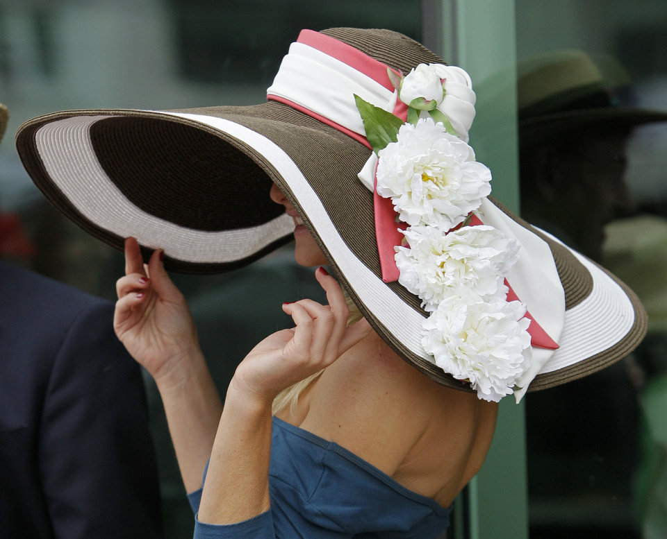 Photo - A spectator shows off her Derby hat before the 137th Kentucky Derby horse race at Churchill Downs Saturday, May 7, 2011, in Louisville, Ky. (AP Photo/Ed Reinke) ORG XMIT: DBY189  Ed Reinke - AP