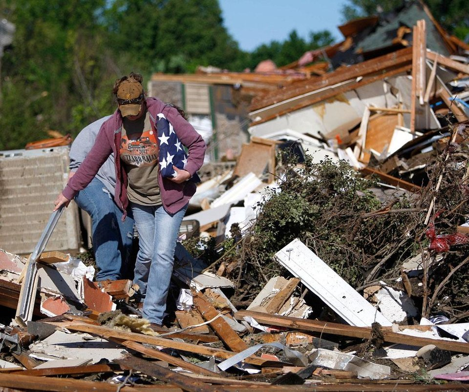 Photo -  Ashley Hort carries her late grandfather's flag out after a tornado struck Woodward, Okla., Sunday, April 15, 2012. Photo by Bryan Terry