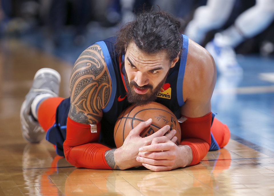 Photo - Oklahoma City's Steven Adams (12) falls on a loose ball during the NBA basketball game between the Oklahoma City Thunder and the Golden State Warriors at Chesapeake Energy Arena,  Saturday, March 16, 2019. Photo by Sarah Phipps, The Oklahoman