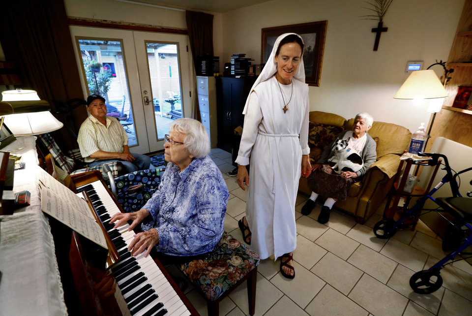 Photo -  Sister Maria Faulkner walks through the living room of the Gospel of Life Dwelling as Annabelle Miller plays piano. [Photo by Steve Sisney, The Oklahoman]