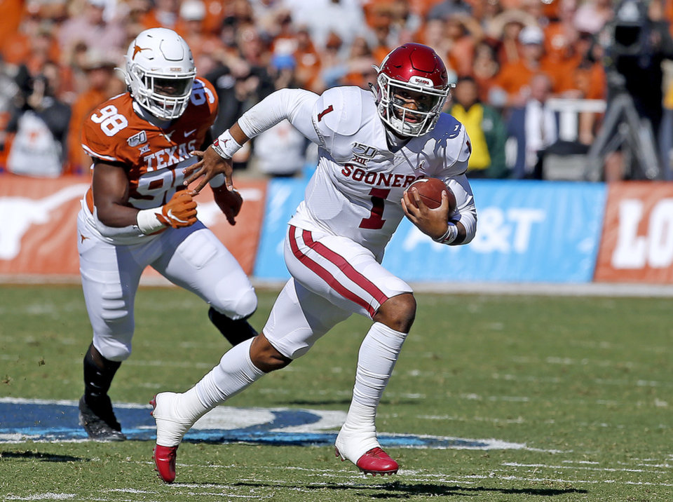 Photo - Oklahoma's Jalen Hurts (1) rushes as Texas's Moro Ojomo (98) chases him in the first quarter during the Red River Showdown college football game between the University of Oklahoma Sooners (OU) and the Texas Longhorns (UT) at Cotton Bowl Stadium in Dallas, Saturday, Oct. 12, 2019. OU won 34-27. [Sarah Phipps/The Oklahoman]