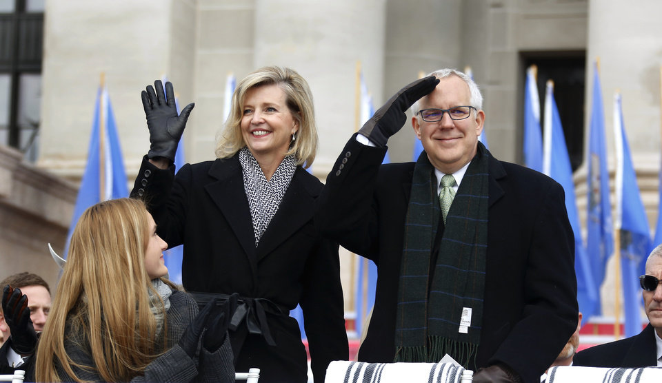 Photo - Gov. Brad Henry and his wife, Kim, stand and wave as former Oklahoma governors are introduced on the platform before Kevin Stitt would follow in their footsteps and be sworn in to become Oklahoma's 28th governor on Monday, Jan. 14, 2019. Photo by Jim Beckel, The Oklahoman.