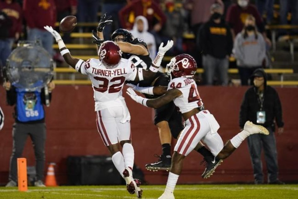 Photo -  Oklahoma defensive back Delarrin Turner-Yell (32) and defensive back Brendan Radley-Hiles, right, break up a pass intended for Iowa State tight end Charlie Kolar, center, during the first half last Saturday. [AP Photo/Charlie Neibergall]