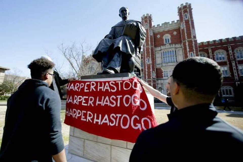 Photo -  University of Oklahoma students hang a sign demanding OU Provost Kyle Harper's resignation on a statue of George Lynn Cross outside Evans Hall as they participate in a sit-in organized by the Black Emergency Response Team at the University of Oklahoma in Norman on Thursday. The protest comes after two incidents where faculty members used a racial slur while teaching. [Bryan Terry/The Oklahoman]