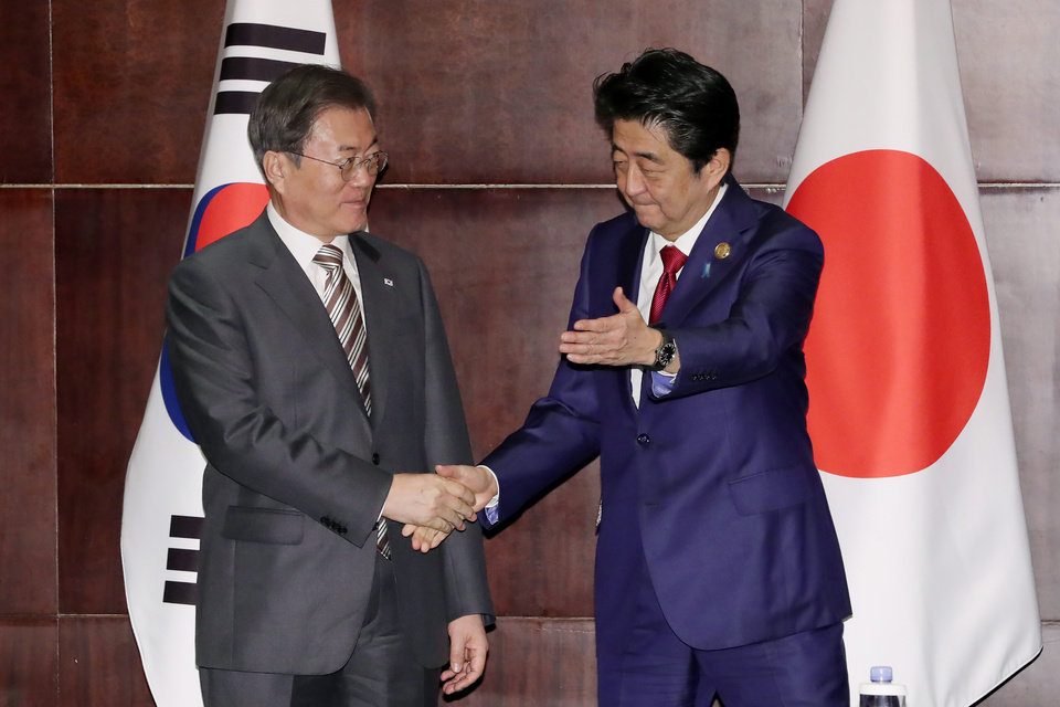 Photo -  South Korean President Moon Jae-in, left, shakes hands wth Japanese Prime Minister Shinzo Abe during a meeting in Chengdu, China, Tuesday, Dec. 24, 2019. (Lee Jin-wook/Yonhap via AP)