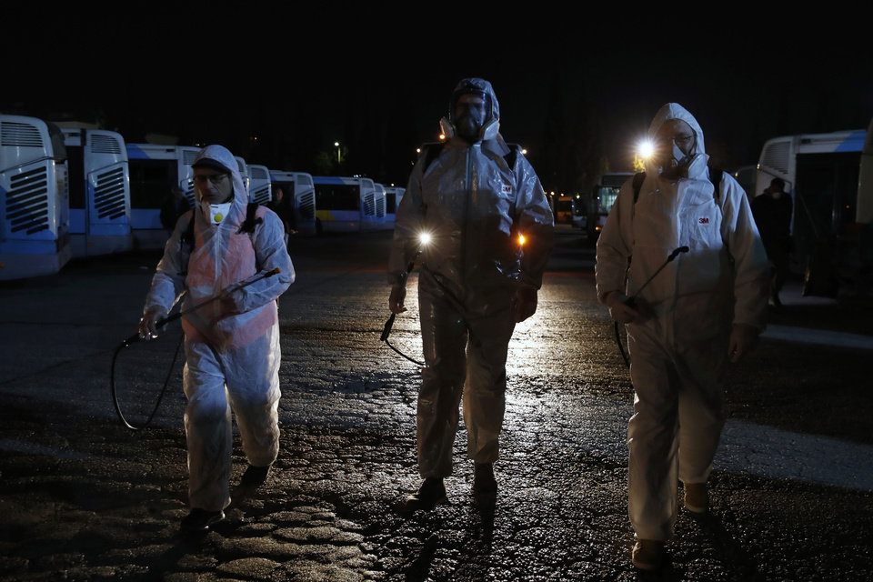 Photo -  Workers wearing protective suits walk at a bus depot before they spray disinfectant inside the vehicles in Athens, Saturday, March 14, 2020. Greece has announced new sweeping closures Friday, closing all shopping malls, cafes, bars and restaurants, except those that provide only take-aways or deliveries. All museums, ancient sites, libraries and beauty salons will also shut down. For most people, the new coronavirus causes only mild or moderate symptoms, such as fever and cough. For some, especially older adults and people with existing health problems, it can cause more severe illness, including pneumonia. (AP Photo/Thanassis Stavrakis)