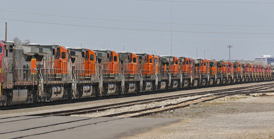 Photo -  Scores of BNSF Railway locomotives are parked in a rail yard near Interstate 235 just north of NW 23 in Oklahoma City. The locomotives have been there for several weeks, and are expected to remain there until rail traffic improves, the company says. [Photo By Steve Gooch, The Oklahoman]