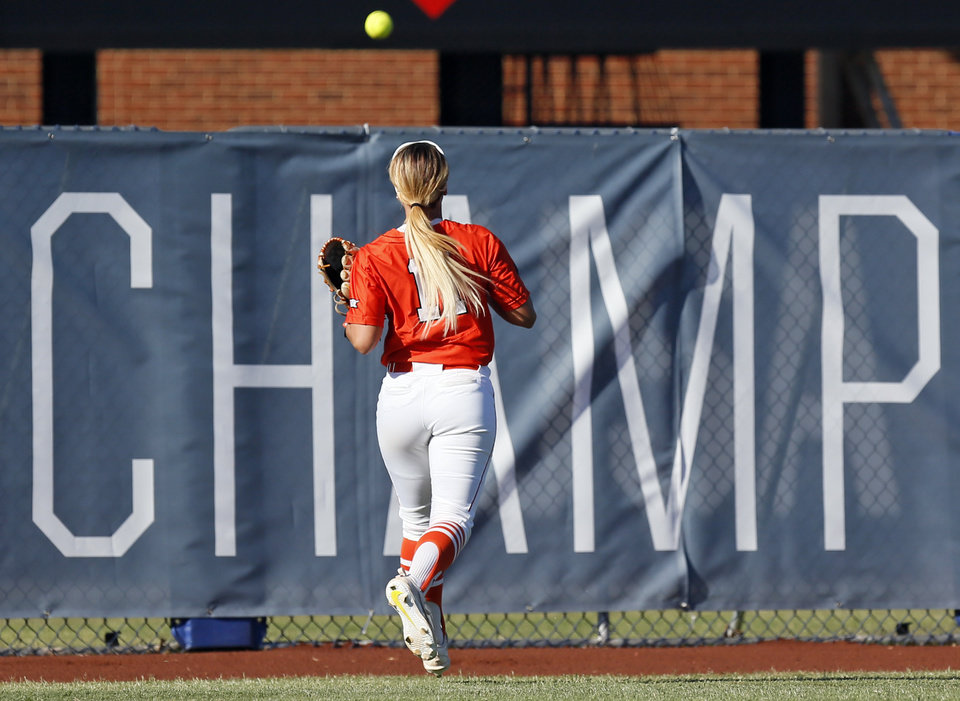 Photo - OSU's Alex Edinger (11) watches a two-run home run by OU's Nicole Pendley (1), not pictured, go over the fence in the fifth inning during the championship game of the Big 12 softball tournament between Oklahoma and Oklahoma State at ASA Hall of Fame Stadium in Oklahoma City, Saturday, May 13, 2017. OU won 2-0. Photo by Nate Billings, The Oklahoman