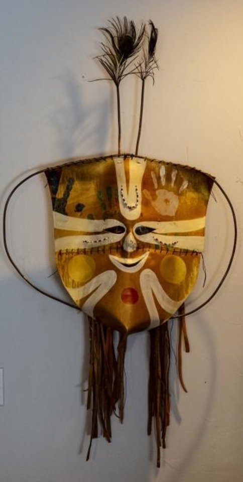 Photo -  A lether mask created by G. Patrick Riley is displayed at his home studio in Bethany on July 29. Riley, who is renowned for his colorful masks, has a variety of his work on view in the exhibit
