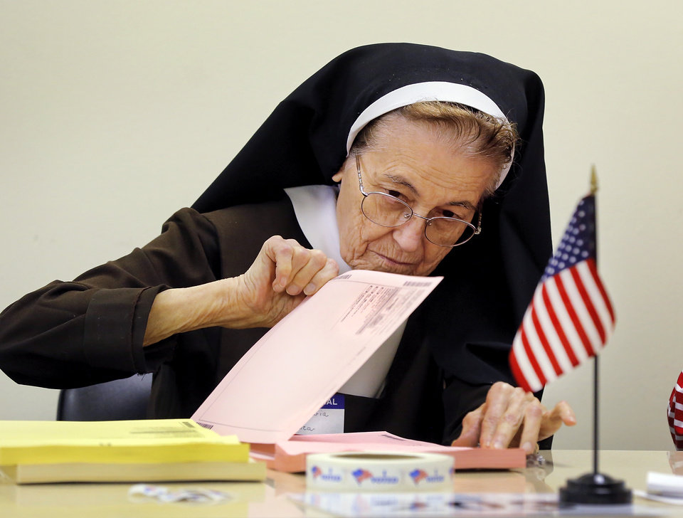 Photo - Poll worker Sister Maria Francesca , a Catholic Carmelite nun, tears a ballot sheet  for a voter to complete at the polling site for precinct  203 at Trinity Baptist Church, on NW 23 just west of Classen Blvd., on Tuesday, June 28, 2016. Francesca said she has volunteered on election day for more than a decade, at various locations. Photo by Jim Beckel, The Oklahoman