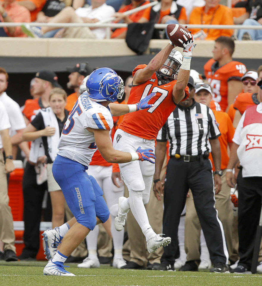 Photo - Oklahoma State's Dillon Stoner (17) catches the ball in front of Boise State's Benton Wickersham (25) during a college football game between the Oklahoma State University Cowboys (OSU) and the Boise State Broncos at Boone Pickens Stadium in Stillwater, Okla., Saturday, Sept. 15, 2018. Oklahoma State won 44-21. Photo by Bryan Terry, The Oklahoman