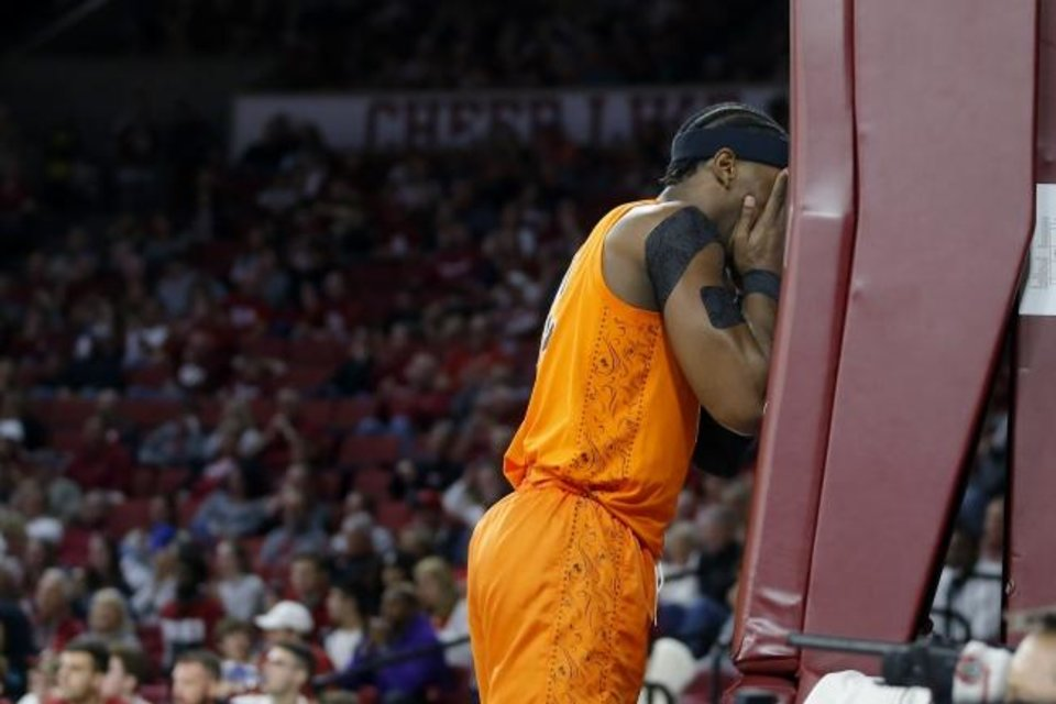 Photo -  Cameron McGriff covers his face under the basket Saturday as his Cowboys fell to 0-8 in Big 12 play. [Bryan Terry/The Oklahoman]