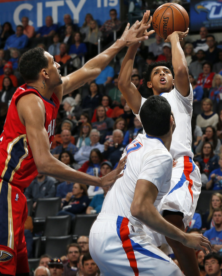 Photo - Oklahoma City's Cameron Payne (22) shoots against New Orleans' Alexis Ajinca (42) near Oklahoma City's Enes Kanter (11) during an NBA basketball game between the New Orleans Pelicans and the Oklahoma City Thunder at Chesapeake Energy Arena in Oklahoma City, Thursday, Feb. 11, 2016.  Photo by Nate Billings, The Oklahoman