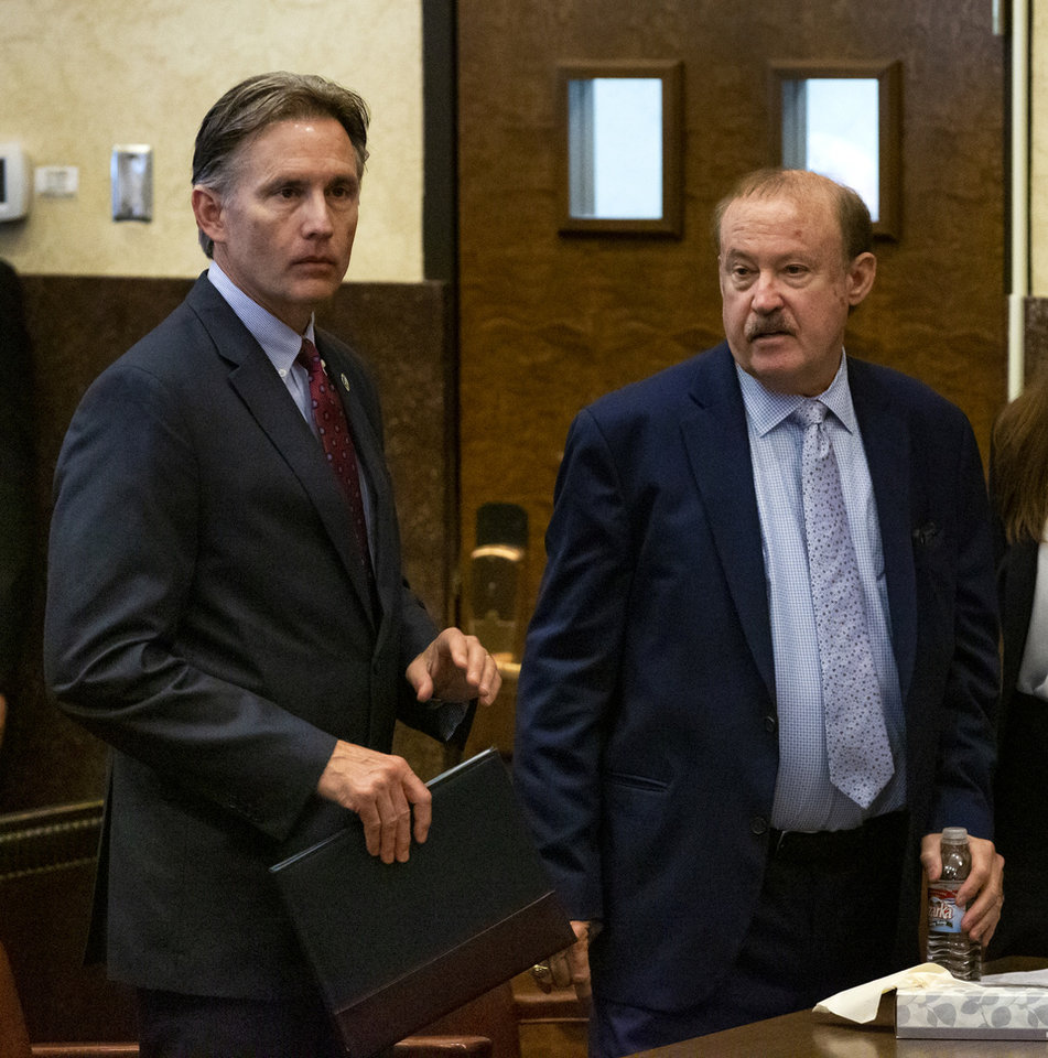 Photo - State's attorney Reggie Whitten, right, and Attorney General Mike Hunter prepare to leave the courtroom after Judge Thad Balkman read a summery of his decision in the opioid trial at the Cleveland County Courthouse in Norman, Okla. on Monday, Aug. 26, 2019. Judge Balkman ruled in favor of the State of Oklahoma, that Johnson and Johnson pay $572 million to a plan to abate the opioid crisis. The proceeding were the first public trial to emerge from roughly 2,000 U.S. lawsuits aimed at holding drug companies accountable for the nationÕs opioid crisis.  [Chris Landsberger/Pool]