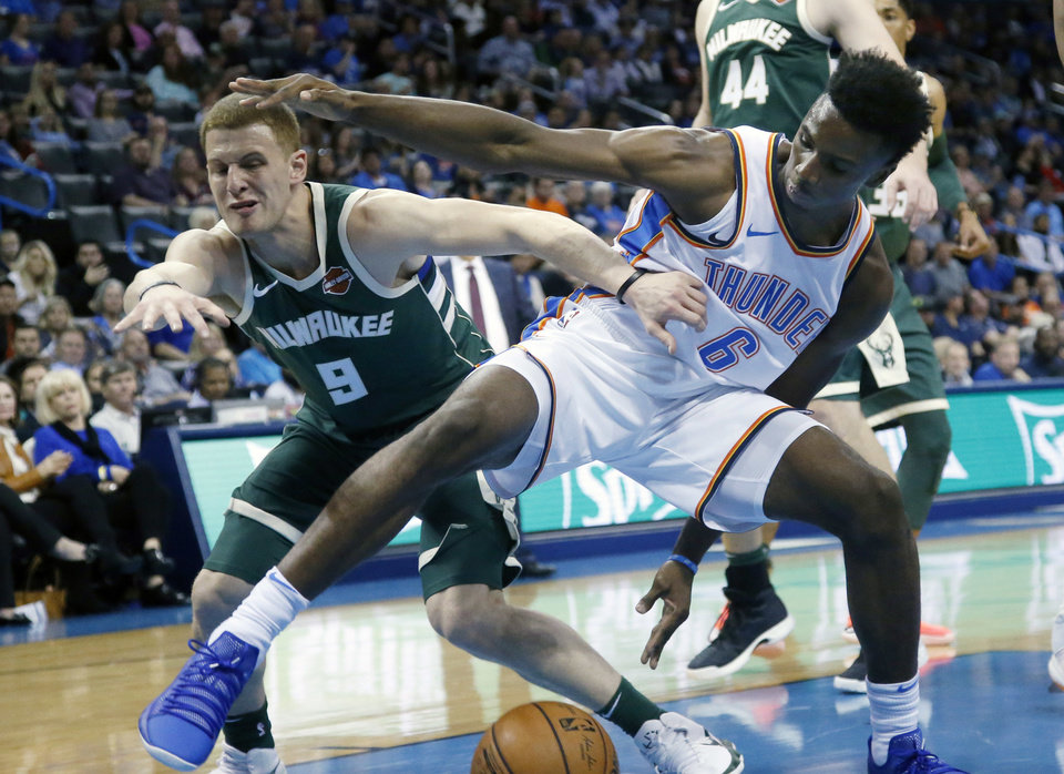 Photo - Milwaukee Bucks guard Donte DiVincenzo (9) and Oklahoma City Thunder guard Hamidou Diallo (6) watch a loose ball in the first quarter of an NBA basketball game in Oklahoma City, Tuesday, Oct. 9, 2018. (AP Photo/Sue Ogrocki)