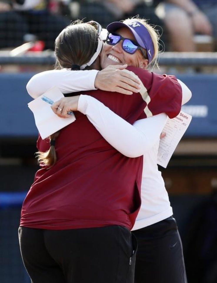 Photo -  Washington coach Heather Tarr, right, and Florida State coach Lonni Alameda hug before the first game of the championship series of the 2018 Women's College World Series. [Nate Billings/The Oklahoman]