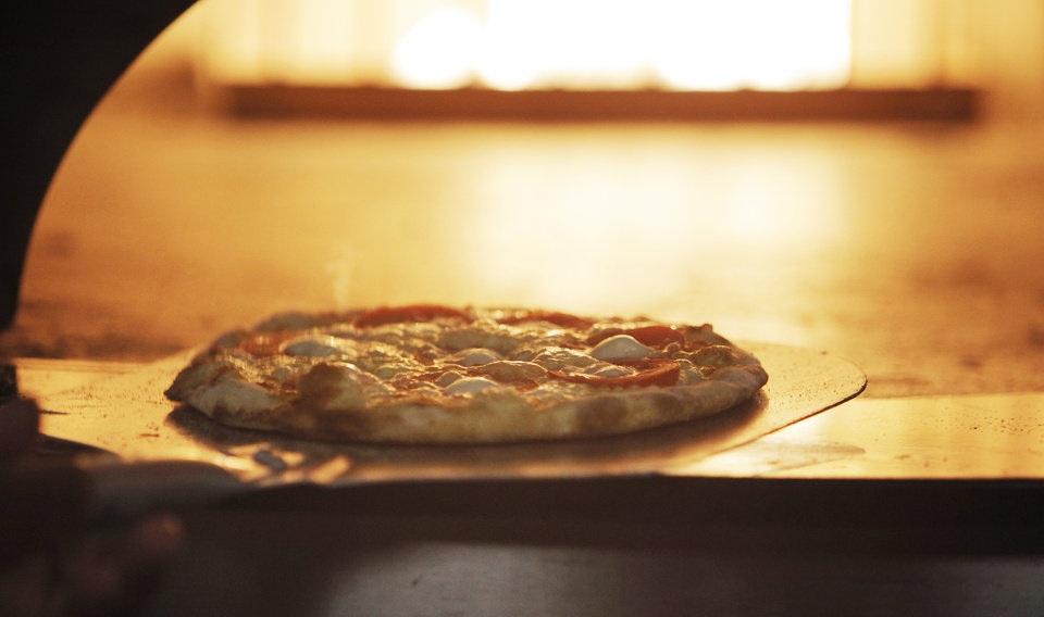 Photo -  A Margherita pizza is removed from the oven at Cafe 501 in the Classen Curve in Oklahoma City, Monday, October 4, 2010. Photo by Nate Billings, The Oklahoman