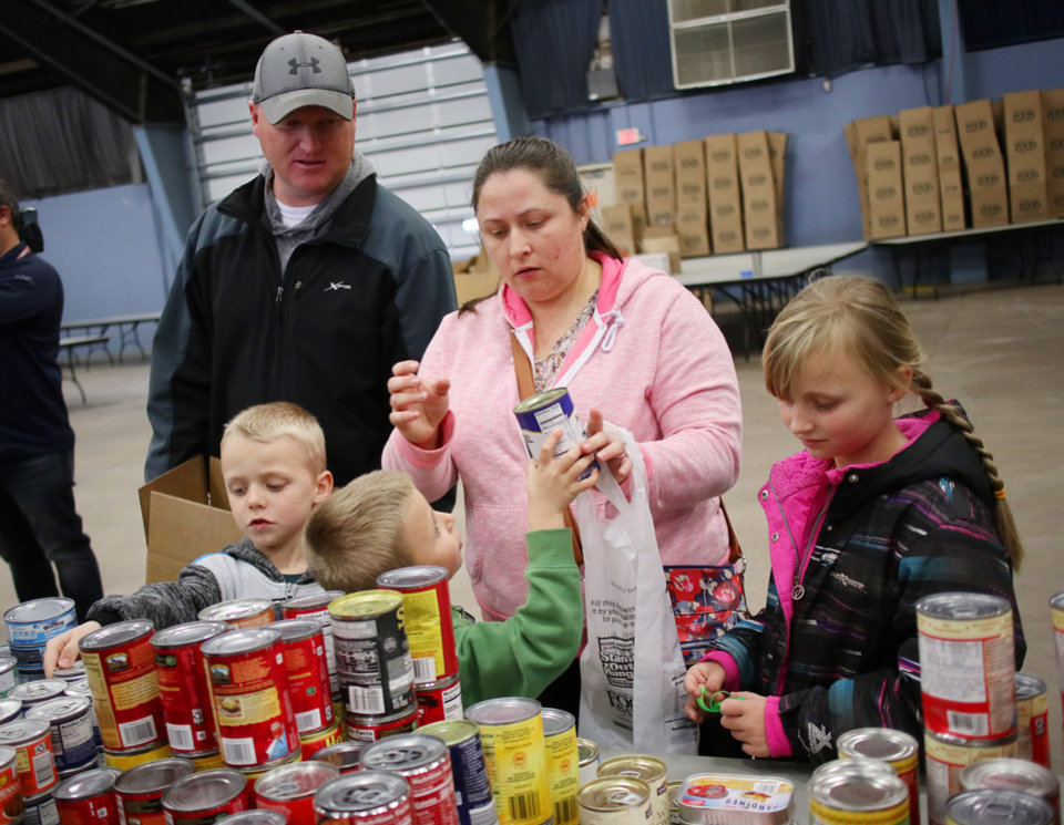 Photo - Newcastle family of Kevin Smith, with wife Lori, Kaitlyn, 8, and twins Kaden and Kasey, 6, make a selection of canned food during a free food distribution for federal employees by the Regional Food Bank of Oklahoma at State Fair Park Monday, January 21, 2019.  Photo by Doug Hoke, The Oklahoman