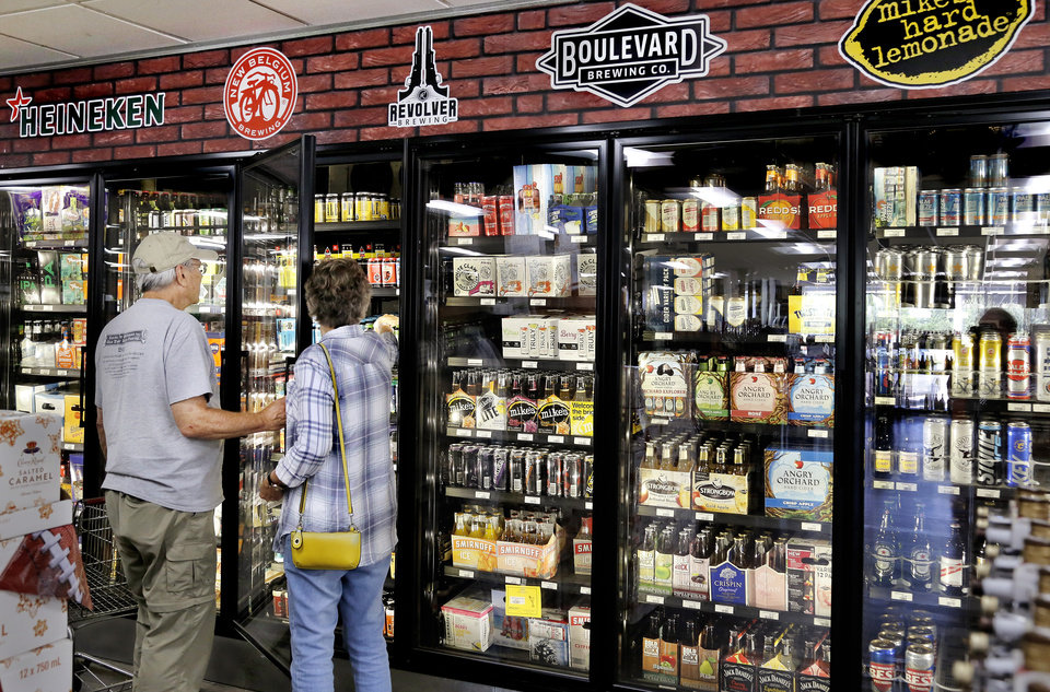 Photo -  Customers shop for beer stored inside new coolers, that aren't turned on, inside Byron's Liquor Warehouse at 2322 N Broadway. [Photo by Jim Beckel, The Oklahoman]