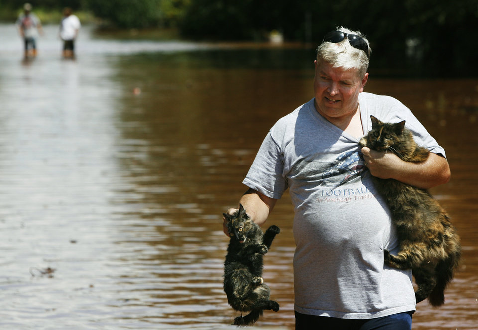 Photo - Marlon Raidt wades through rising floodwaters after rescuing two cats on Sunday, August 19, 2007, in Kingfisher, Okla. By James Plumlee, The Oklahoman.
