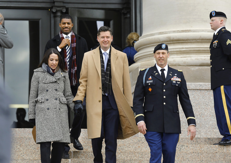 Photo - Oklahoma City Mayor David Holt and wife, Rachel are escorted to their seats on the platform where they attended inauguration ceremony where Kevin Stitt was sworn in as Oklahoma's 28th governor by Supreme Court Chief Justice Noma Gurich on Monday, Jan. 14, 2019. Behind the couple is  J. D. Baker, special assistant to the mayor. Photo by Jim Beckel, The Oklahoman.