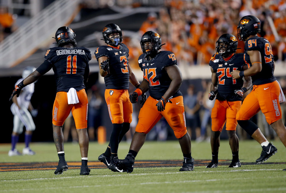 Photo - Oklahoma State's Amen Ogbongbemiga (11), Tre Sterling (3), Jayden Jernigan (42), Jarrick Bernard (24) and Trace Ford (94) celebrate a play during the college football game between the Oklahoma State Cowboys and the Kansas State Wildcats at Boone Pickens Stadium in Stillwater, Okla., Saturday, Sept. 28, 2019.  OSU won 26-13. [Sarah Phipps/The Oklahoman]