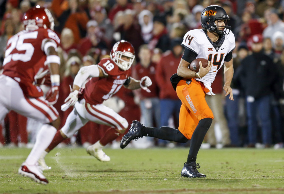 Photo - Oklahoma State's Taylor Cornelius (14) carries the ball for a first down in the fourth quarter of a Bedlam college football game between the University of Oklahoma Sooners (OU) and the Oklahoma State University Cowboys (OSU) at Gaylord Family-Oklahoma Memorial Stadium in Norman, Okla., Nov. 10, 2018. OU won 48-47. Photo by Nate Billings, The Oklahoman