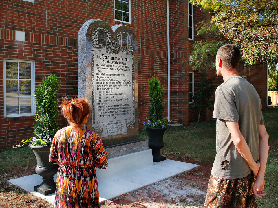 "Photo - Deborah Ashcraft  left, of Yale, and Johnny Davis of Pawnee, spend a few minutes Tuesday afternoon, Oct. 5, 2015,  to view the newly located Ten Commandments Monument after it was removed overnight from the grounds of the Capitol. When asked what their impression was of the monument's current placement, both said they liked it and said it looks good there.  Governor Mary Fallin, state Representative Mike Ritze and the Oklahoma Council of Public Affairs (OCPA) announced the relocation of the Ten Commandments monument from the Oklahoma State Capitol to OCPAÃ•s campus, located on private property on the northwest corner of NE 13 and Lincoln Blvd., ten blocks south of the capitol complex. The Oklahoma Supreme Court ordered the monument to be removed from the Capitol grounds in June, saying the Oklahoma Constitution prohibited the state from displaying it. The state appealed that decision but could not get the Supreme Court ruling overturned. Fallin thanked OCPA for housing the monument and said she would work with lawmakers to put a proposed Constitutional change to a vote of the people, allowing the monument to eventually return to the Capitol.  OCPA is a public policy research organization that focuses on state-based issues from a perspective of limited government, individual liberty and a free-market economy. Ã'OCPA has been committed to providing solutions to make Oklahoma a better state for more than 22 years,Ã"" said Michael Carnuccio, president of OCPA. Ã'Typically, we do so with fact-based research and ideas rooted in free enterprise and the rule of law. Today, however, we are pleased to provide a home for the monument while lawmakers pursue legislative solutions that allow it to be returned to the Capitol grounds.Ã""  Rep. Ritze raised the private dollars to create the monument and then gifted it to the state. Photo by Jim Beckel, The Oklahoman."